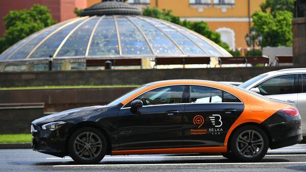 Машина службы каршеринга Belka Car едет по Моховой улице в Москве