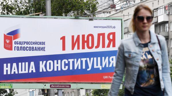 Прохожая около баннера, информирующего об общероссийском голосовании по поправкам в Конституцию РФ, в Новосибирске
