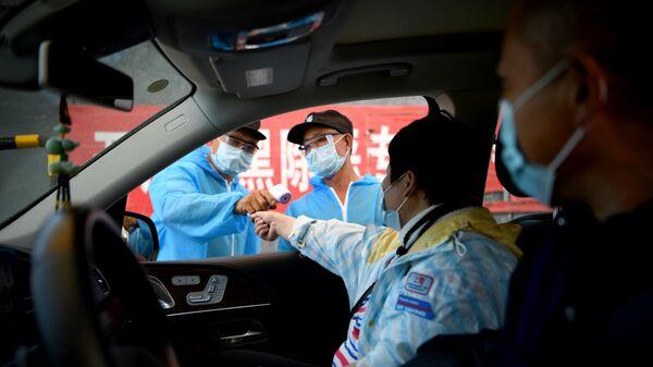 Сотрудник Службы безопасности в защитном костюме проверяет температуру людей, въезжающих на рынок Синьфади в Пекине, Китай