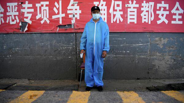 Охранник в защитной костюме на контрольно-пропускном пункте на рынке Синьфади в Пекине, Китай