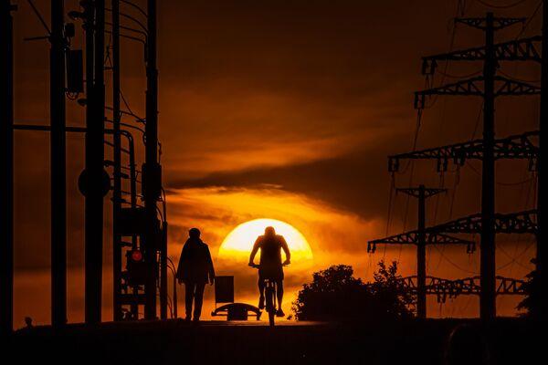 Мужчина едет на велосипеде по одной из улиц в Москве