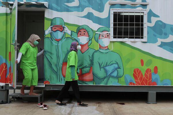 Медицинские работники выходят из лаборатории в Джакарте, Индонезия