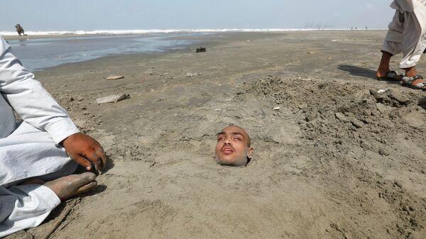 Мужчина, закопанный в песок, наблюдает солнечное затмение в Карачи, Пакистан