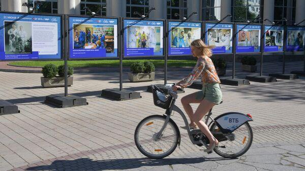 Девушка едет на велосипеде мимо экспозиции, организованной в рамках акции Спасибо медработникам, в Москве