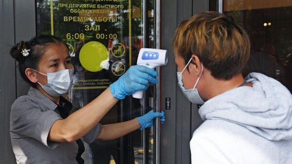 Измерение температуры сотрудникам Макдоналдса, пришедшим на смену