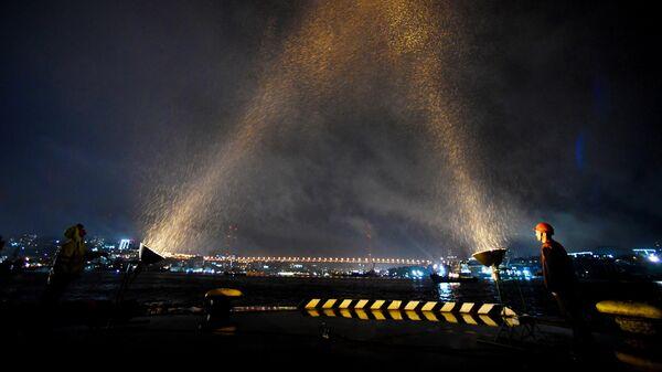 Портовики освещают небо прожекторами на третьем причале Владивостокского морского торгового порта (ВМТП) во время акции Лучи Победы во Владивостоке