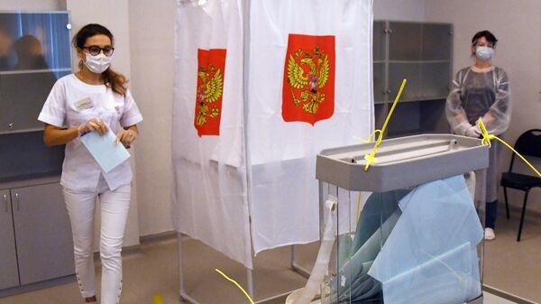 Медицинский работник принимает участие в голосовании по внесению поправок в Конституцию РФ на избирательном участке в Приморском краевом перинатальном центре (ГБУЗ ПКПЦ) во Владивостоке
