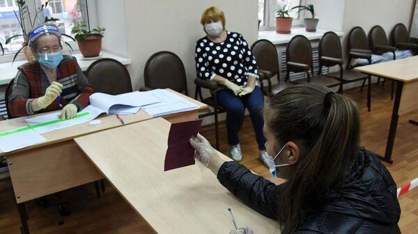 Член избирательной комиссии регистрирует участницу голосования по внесению поправок в Конституцию РФ на избирательном участке №727 во Владивостоке