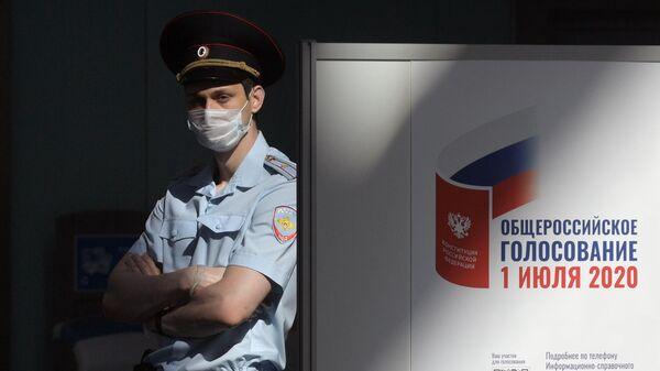 Полицейский на избирательном участке во время голосования по внесению поправок в Конституцию РФ