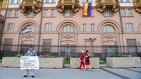 Одиночный пикет у здания посольства США в Москве, на котором вывешен флаг ЛГБТ-сообщества