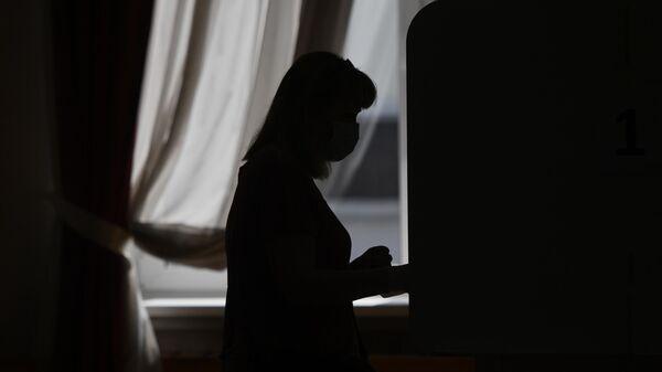 Девушка во время голосования по вопросу принятия поправок в Конституцию РФ на избирательном участке в Москве