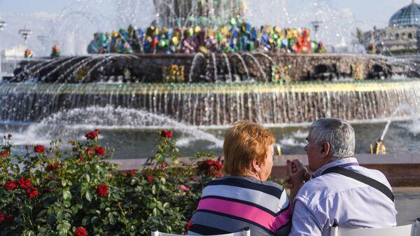 Люди отдыхают у фонтана Дружба народов на ВДНХ в Москве