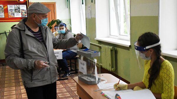 Мужчина во время голосования на избирательном участке по вопросу внесения поправок в Конституцию РФ во Владивостоке
