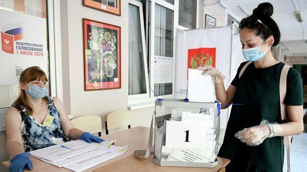 Девушка принимает участие в голосовании по внесению поправок в Конституцию РФ