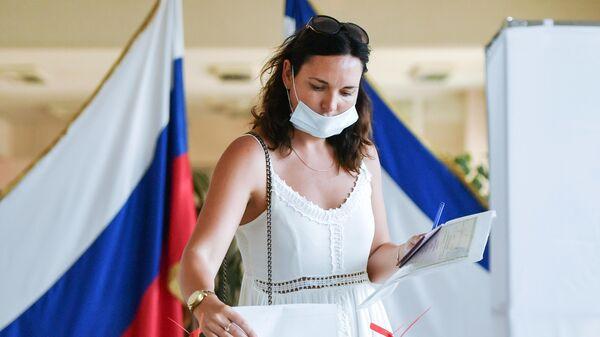 Женщина принимает участие в голосовании по внесению поправок в Конституцию РФ на одном из избирательных участков