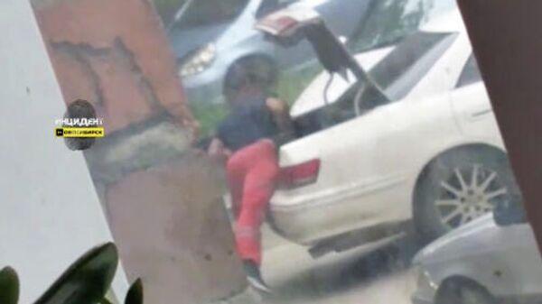 Кадр видео очевидца, на котором мужчину заталкивают в багажник автомобиля в Новосибирске
