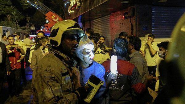 Пожарный помогает пострадавшей женщине на месте взрыва в медицинской клинике в Тегеране