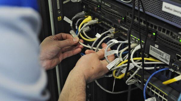 Инженер отдела эксплуатации информационных систем и платформ проводит настройку оборудования