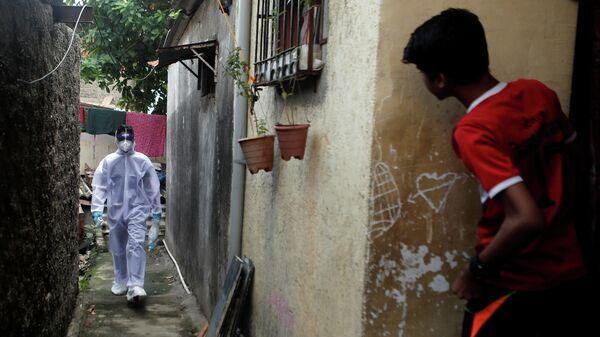 Медицинский работник в защитном костюме идет по улице в Мумбаи, Индия