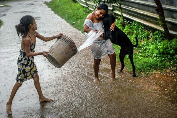 Девочки играют под дождем в Гаване, Куба
