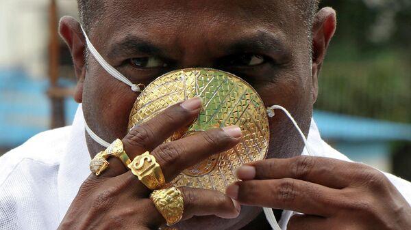 Житель индийского штата Махараштра Шанкар Кураде носит золотую защитную маску на фоне распространения коронавируса