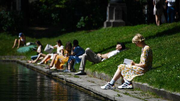 Люди в жаркий день отдыхают на Патриарших прудах в Москве
