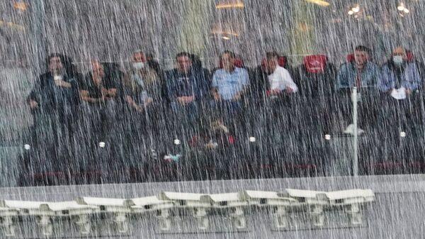 Болельщики на трибуне наблюдают во время дождя за ходом матча РПЛ Спартак — Локомотив