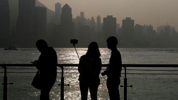 Пара делает селфи во время заката с видом на финансовый Центральный район Гонконга
