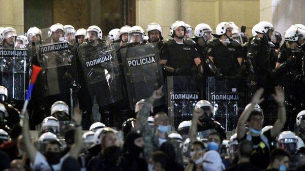Участники акции протеста и сотрудники правоохранительных органов в центре Белграда