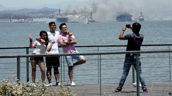 Люди фотографируются на фоне горящего универсального десантного корабля USS Bonhomme Richard (LHD 6)