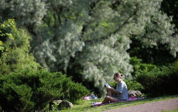 Девушка читает книгу в парке Дубки в Москве