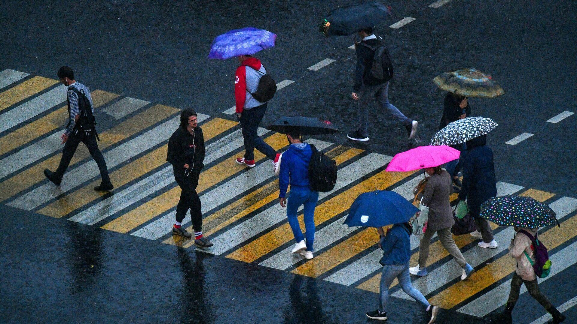 Прохожие переходят через дорогу во время грозы на одной из улиц в Москве - РИА Новости, 1920, 12.06.2021