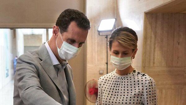 Президент Сирии Башар Асад и его супруга Асма во время голосования на парламентских выборах на избирательном участке в министерстве по делам президента в Дамаске