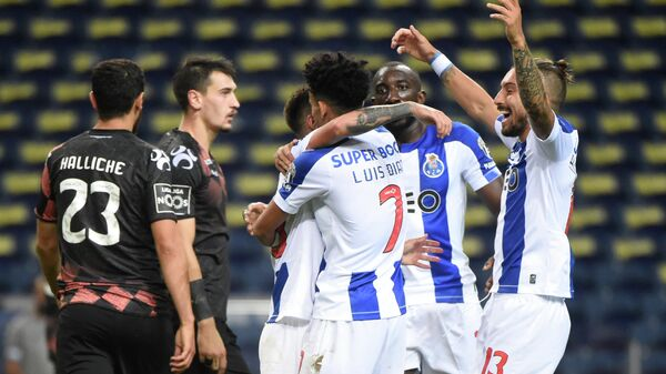 FC Porto's Brazilian midfielder Otavinho celebrates with teammates after scoring a goal during the Portuguese League football match FC Porto against Moreirense FC at the Dragao stadium in Porto on July 20, 2020. (Photo by MIGUEL RIOPA / AFP)