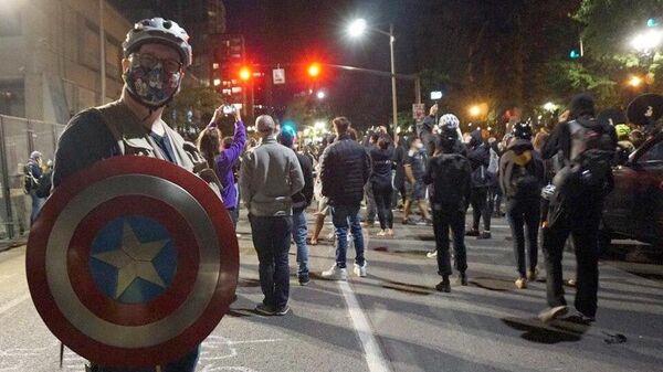 Участник акции протеста на одной из улиц в Портленде