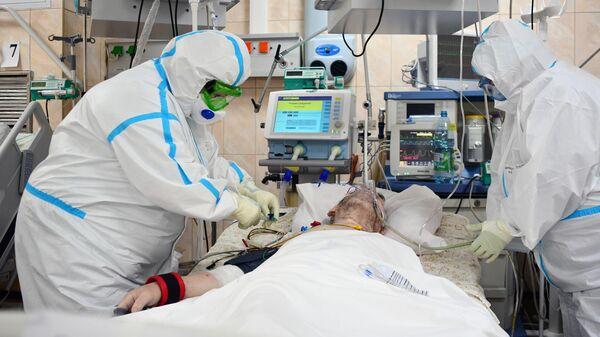 Медицинские работники и пациент в отделении реанимации и интенсивной терапии госпиталя COVID-19 городской клинической больницы № 15 имени О. М. Филатова
