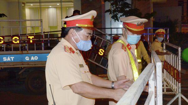 Полицейские в защитных масках перекрывают улицу в городе Дананг