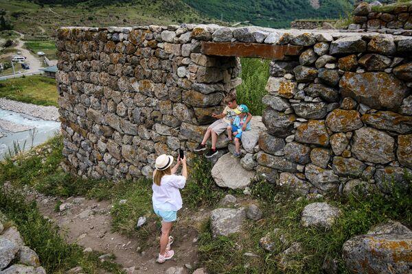 Туристы фотографируются на развалинах Аланского поселения 10 века в ауле Верхняя Балкария в Кабардино-Балкарии