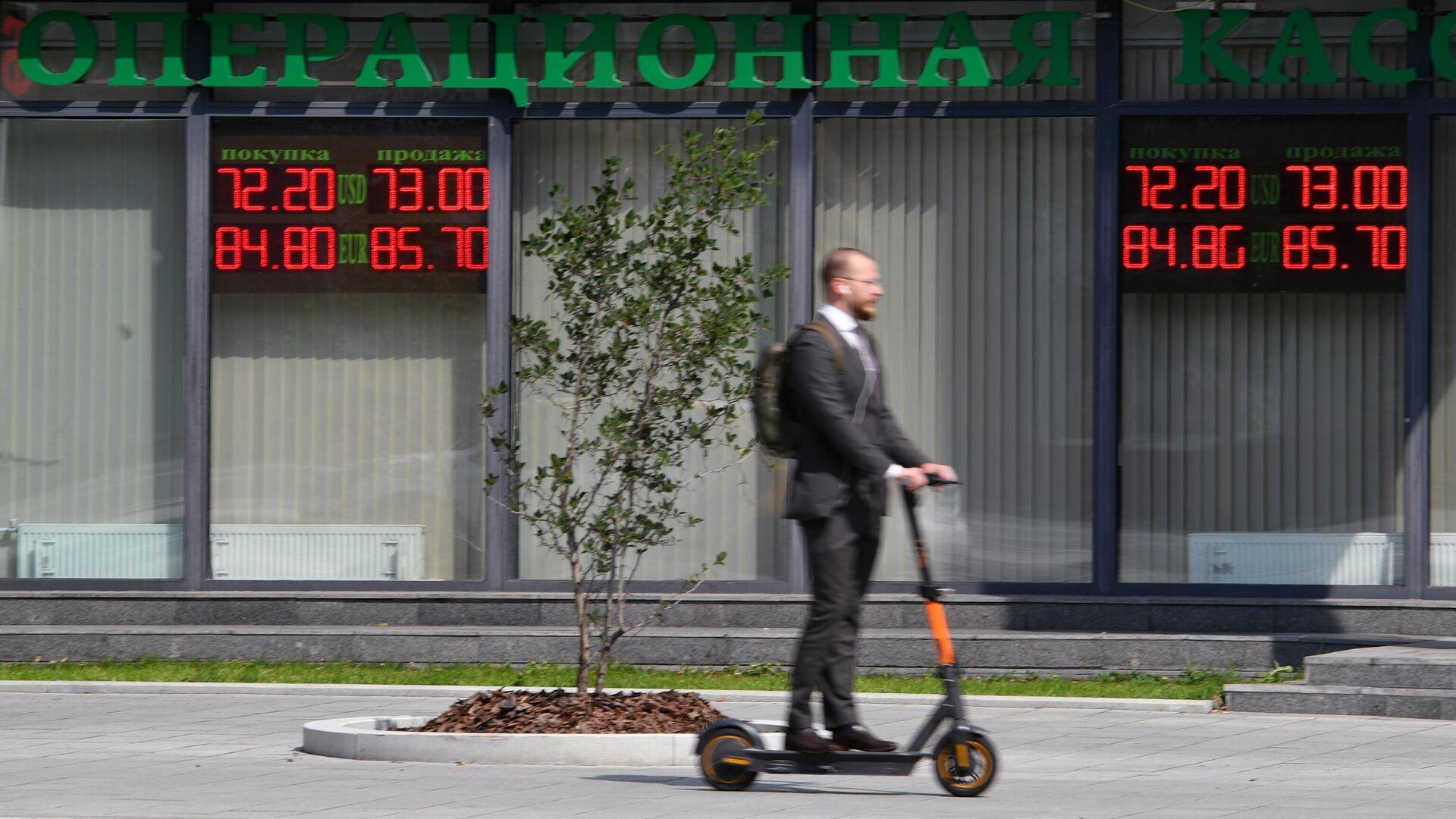 Мужчина около электронного табло с курсами валют в Москве - РИА Новости, 1920, 18.11.2020