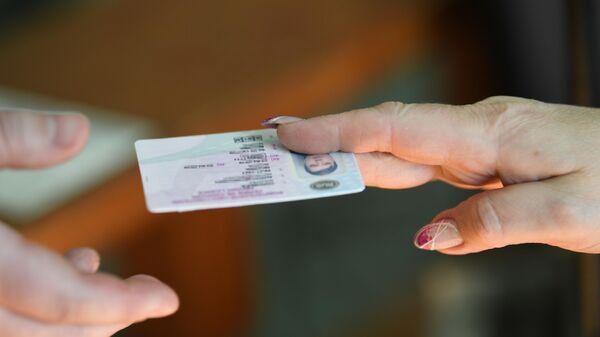 Мужчина получает водительское удостоверение в отделении ГИБДД