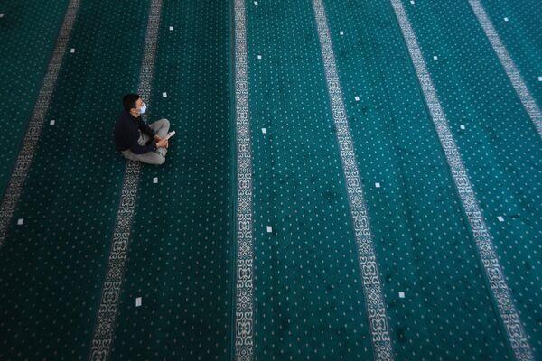 Верующий перед началом праздничной молитвы в Соборной мечети Новосибирска
