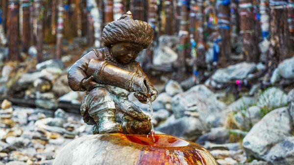 Бронзовая скульптура мальчика с кувшином, из которого льется целебная вода в Тункинском районе республики Бурятия