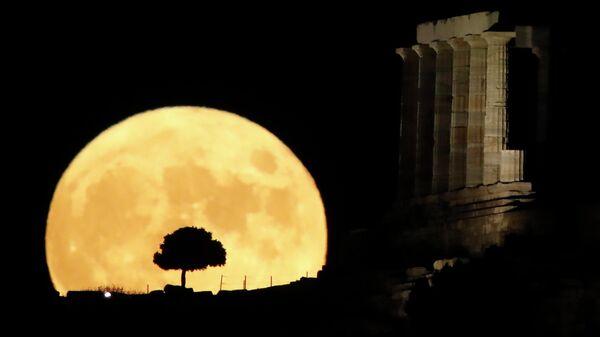 Полная луна за храмом Посейдона на мысе Сунион недалеко от Афин, Греция