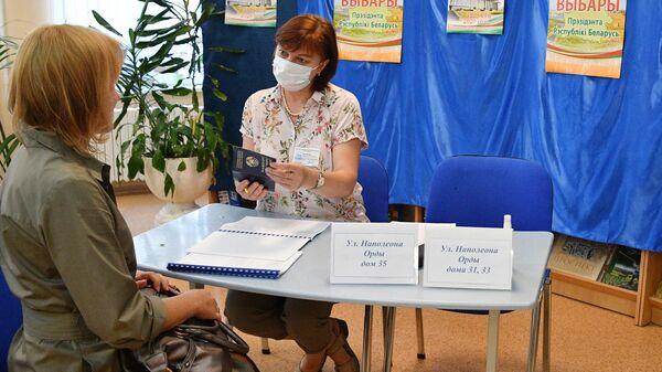 Девушка  досрочно голосует на выборах президента Белоруссии на избирательном участке в Минске