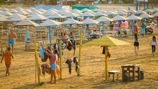 Отдыхающие на пляже в поселке Бузовна в Азербайджане