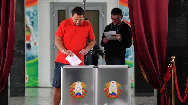 Мужчина голосует на выборах президента Белоруссии на избирательном участке в Минске
