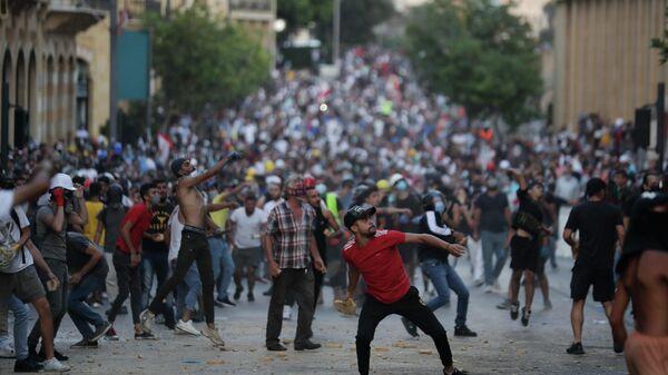 Люди бросают камни во время протеста в Бейруте, Ливан. 9 августа 2020