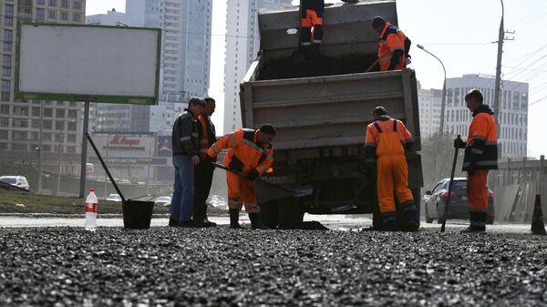 Рабочие проводят ремонт дорожного покрытия