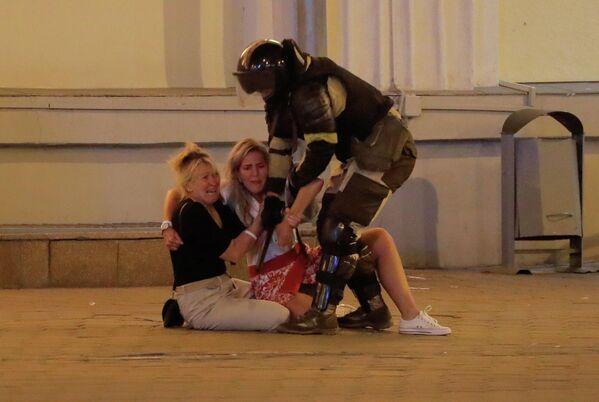 Сотрудник правоохранительных органов с протестующими женщинами во время массовой акции протеста после президентских выборов в Минске, Беларусь