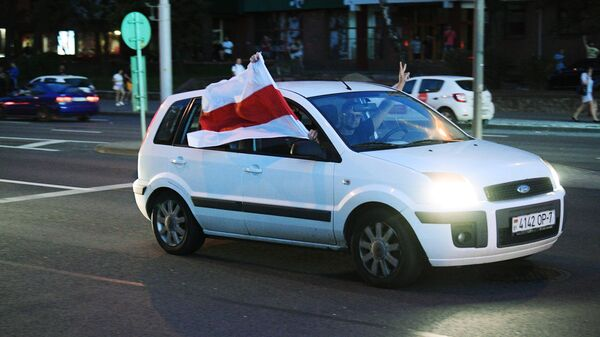 Автомобиль с флагом Республики Беларусь (образца 1991-1995 годов) едет по улице Минска во время акции протеста после президентских выборов